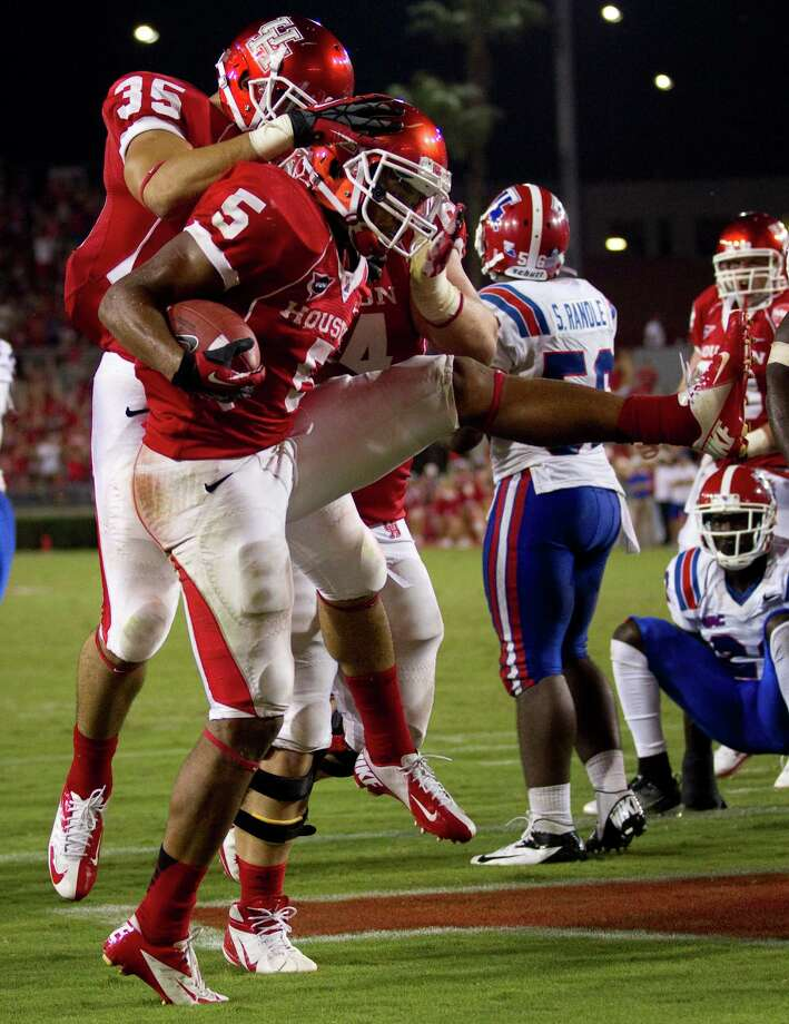 Houston running back Charles Sims (5) and running back Kenneth Farrow (35) celebrate Sims' 2-yard touchdown run during the second quarter in an NCAA football game against Louisiana Tech at Robertson Stadium, Saturday, Sept. 8, 2012, in Houston. Photo: Brett Coomer, Houston Chronicle / © 2012  Houston Chronicle