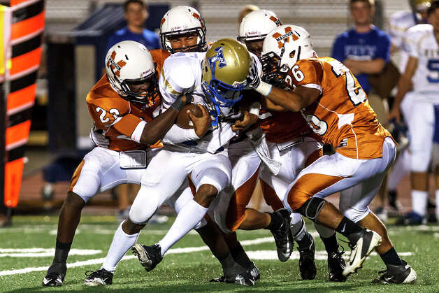 Kerrville Tivy's Jevon Gardner is brought down by Madison's Kevon Giles (from left) HNahum Olivares, Latrell Sledge and Corey Henley during the third quarter of their game at Comalander Stadium on Sept. 8, 2012.  Madison won the game 44-14.  MARVIN PFEIFFER/ mpfeiffer@express-news.net Photo: MARVIN PFEIFFER, Express-News / Express-News 2012