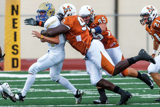 Madison defensive end Vincent Taylor (center) sacks Kerrville Tivy quarterback Parks McNeil during their game at Comalander Stadium on Sept. 8, 2012. Madison won the game 44-14.  MARVIN PFEIFFER/ mpfeiffer@express-news.net Photo: MARVIN PFEIFFER, Express-News / Express-News 2012