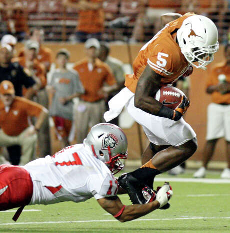 New Mexico's Freddie Young tries to make a shoestring tackle of Texas' Jeremy Hills on Saturday night. Photo: Edward A. Ornelas / © 2012 San Antonio Express-News