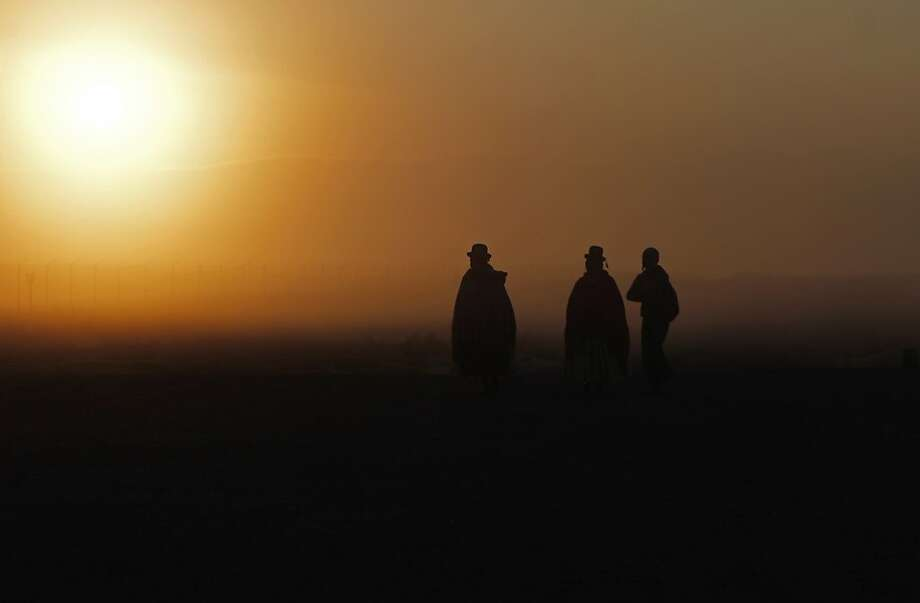 Aymara Indians are silhouetted in the early morning sky as they make their way to the temple of stone walls to attend the wedding of Bolivia's Vice President Alvaro Garcia Linera and Claudia Fernandez in the highlands of Tiwanaku, Bolivia, Saturday, Sept. 8, 2012. The 49-year-old vice president and the 25-year-old journalist were wed by Aymaran spiritual guides at an ancestral site constructed by the ancient Aymara people some 3,000 years ago to observe the heavens. Photo: Juan Karita, Associated Press