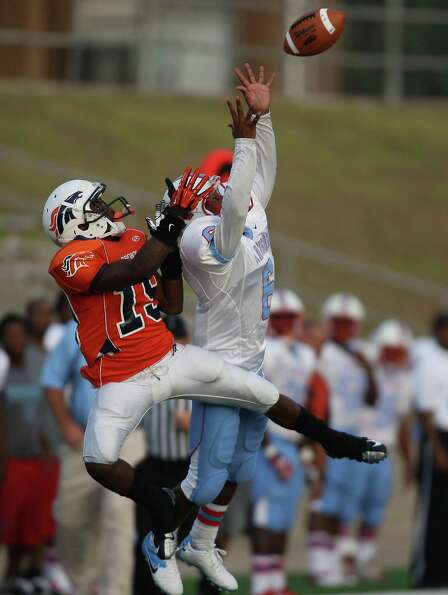 Bush wide receiver Wayne Grice (left) and Madison's Jerard Wiltz go up for a pass from Bush quarterb