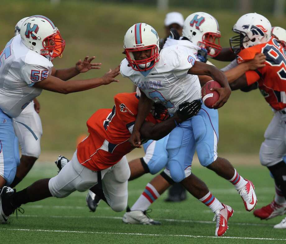 Madison's Jerrell garner (2) is tackled by Bush's Stanley Nzeadibe during the first half of a high school football game, Saturday, September 8, 2012, at Mercer Stadium in Sugar Land, TX. Photo: Eric Christian Smith, For The Chronicle