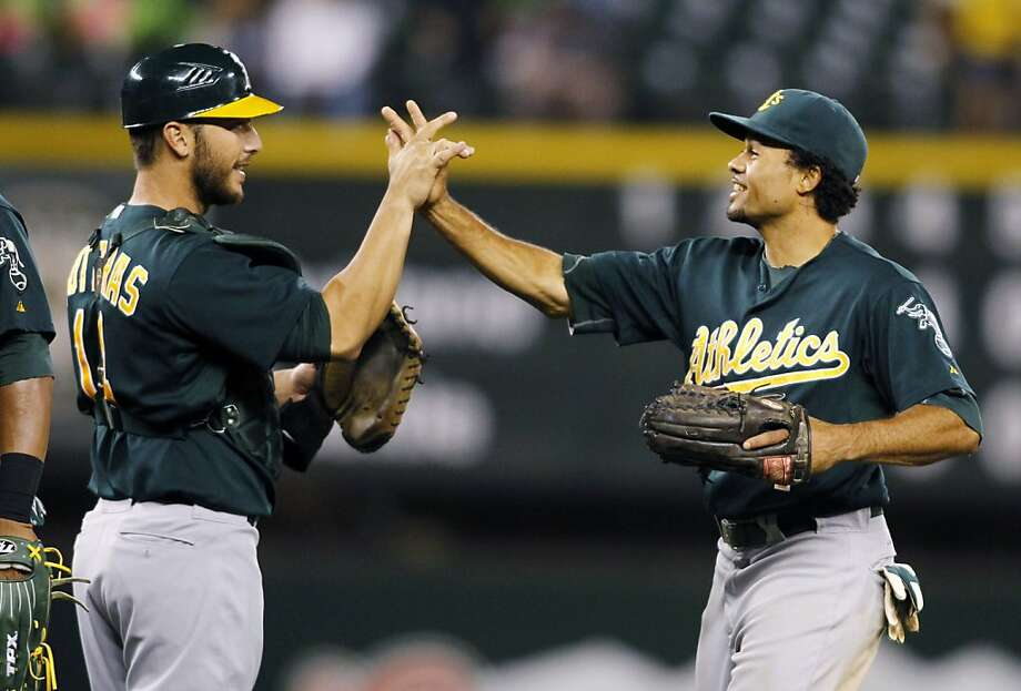 Oakland Athletics' George Kottaras, left, and Coco Crisp celebrate their 6-1 win over the Seattle Mariners in a baseball game in Seattle, Saturday, Sept. 8, 2012. (AP Photo/John Froschauer) Photo: John Froschauer, Associated Press