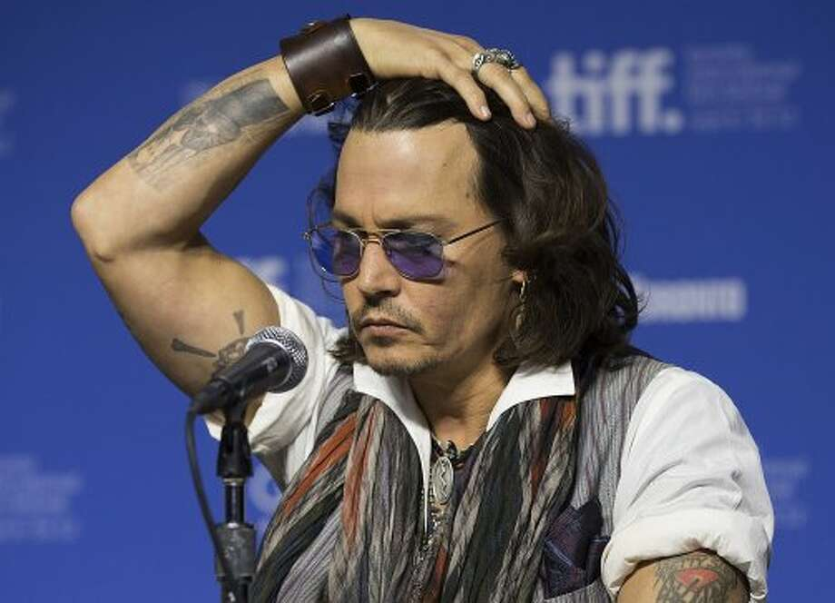 "Actor Johnny Depp gestures a press conference to show his support for the documentary ""West of Memphis."" (ASSOCIATED PRESS)"