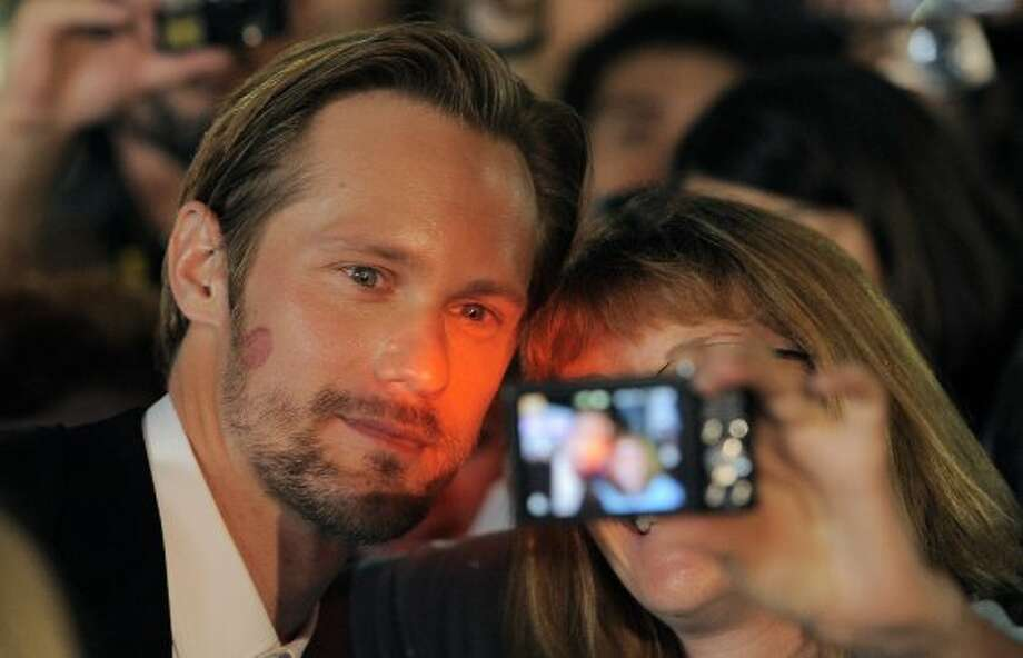 "Alexander Skarsgard, a cast member in the film ""What Maisie Knew,"" poses for a photo with a fan at the premiere of the film. (CHRIS PIZZELLO/INVISION/AP)"