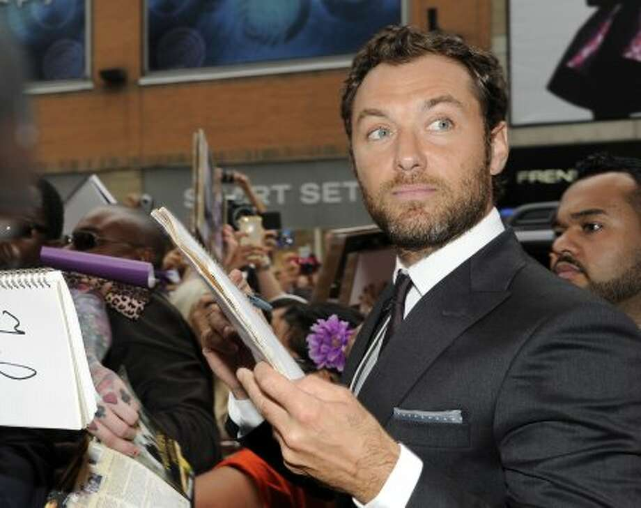 "Actor Jude Law signs autographs before  the premiere of ""Anna Karenina,"" (EVAN AGOSTINI /INVISION/AP)"