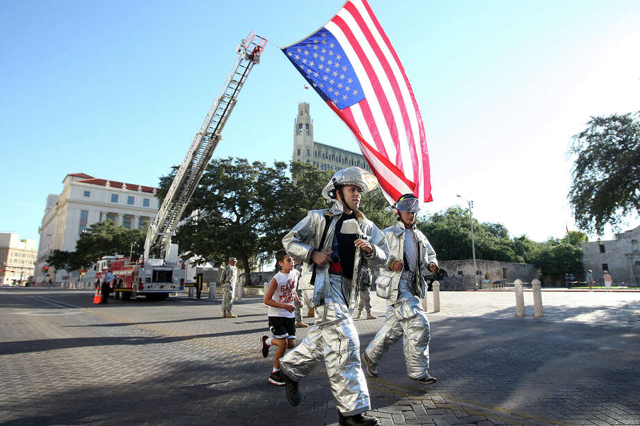 In silver bunker suits, Randolph Air Force Base Firefighters Brandon Sherouse, left, and Darren Fehlinger, right, run with Fehlinger's son, Connery, (cq), during the Stephen Siller Tunnel to Towers Run San Antonio 5K at Alamo Plaza, Sunday, Sept. 9, 2012. The top runner in each division will compete in the Tunnel to Towers run in New York City. Siller was a firefighter with the Brooklyn's Squad 1 and died during the attack on the Twin Towers. Photo: Jerry Lara, San Antonio Express-News / © 2012 San Antonio Express-News
