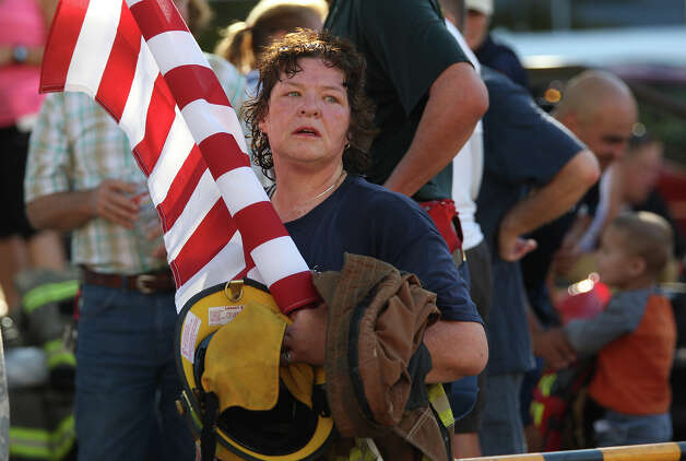 Sandy Oaks Volunteer Fire Department's Terry Place holds the flag she carried in the Stephen Siller Tunnel to Towers Run San Antonio 5K at Alamo Plaza, Sunday, Sept. 9, 2012. The top runner in each division will compete in the Tunnel to Towers run in New York City. Siller was a firefighter with the Brooklyn's Squad 1 and died during the attack on the Twin Towers. Photo: Jerry Lara, San Antonio Express-News / © 2012 San Antonio Express-News