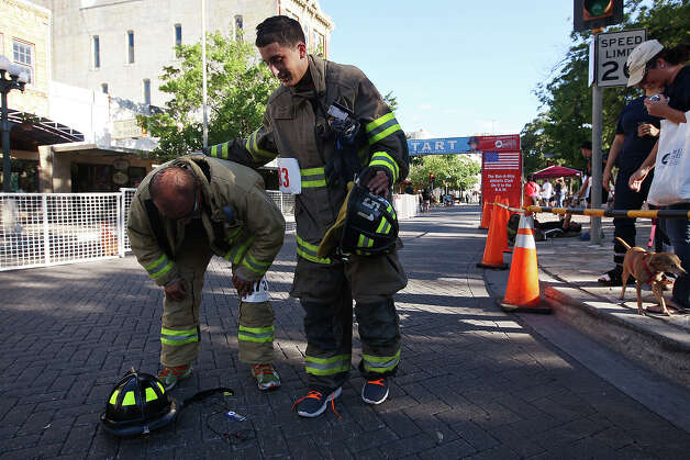 Camelot Volunteer Fire and Rescue's Victor Valencia, right, checks on Leon Valley Deputy Fire Marshal Luiz Valdez after they finish the Stephen Siller Tunnel to Towers Run San Antonio 5K at Alamo Plaza, Sunday, Sept. 9, 2012. The top runner in each division will compete in the Tunnel to Towers run in New York City. Siller was a firefighter with the Brooklyn's Squad 1 and died during the attack on the Twin Towers. Photo: Jerry Lara, San Antonio Express-News / © 2012 San Antonio Express-News