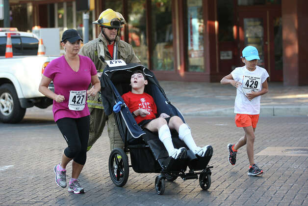 San Antonio Fire Department's Dan Dickerson runs with his family from left, Suzanne, Ryan, 14, and Sarah, 10, during the Stephen Siller Tunnel to Towers Run San Antonio 5K at Alamo Plaza, Sunday, Sept. 9, 2012. The top runner in each division will compete in the Tunnel to Towers run in New York City. Siller was a firefighter with the Brooklyn's Squad 1 and died during the attack on the Twin Towers. Photo: Jerry Lara, San Antonio Express-News / © 2012 San Antonio Express-News