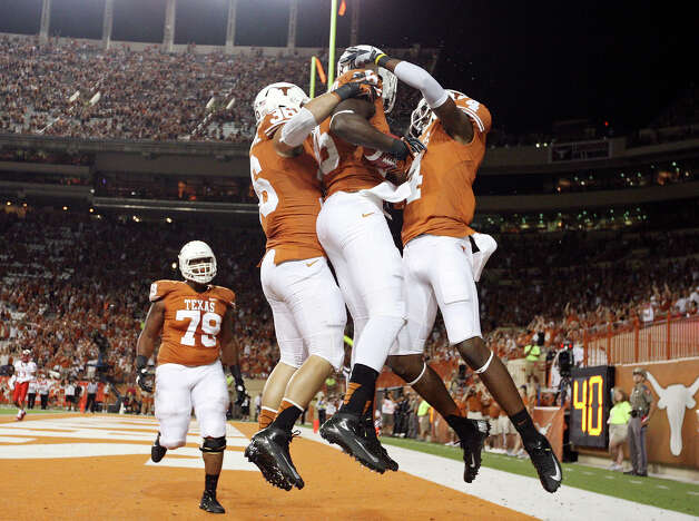 Texas Longhorns'  M.J. McFarland (center) celebrates with teammates Texas Longhorns' Alex De La Torre (left) and Texas Longhorns' Cayleb Jones after scoring a touchdown against the New Mexico Lobos during second half action Saturday Sept. 8, 2012 at Texas Memorial Stadium in Austin, Tx. The Longhorns won 45-0. Photo: Edward A. Ornelas, Express-News / © 2012 San Antonio Express-News