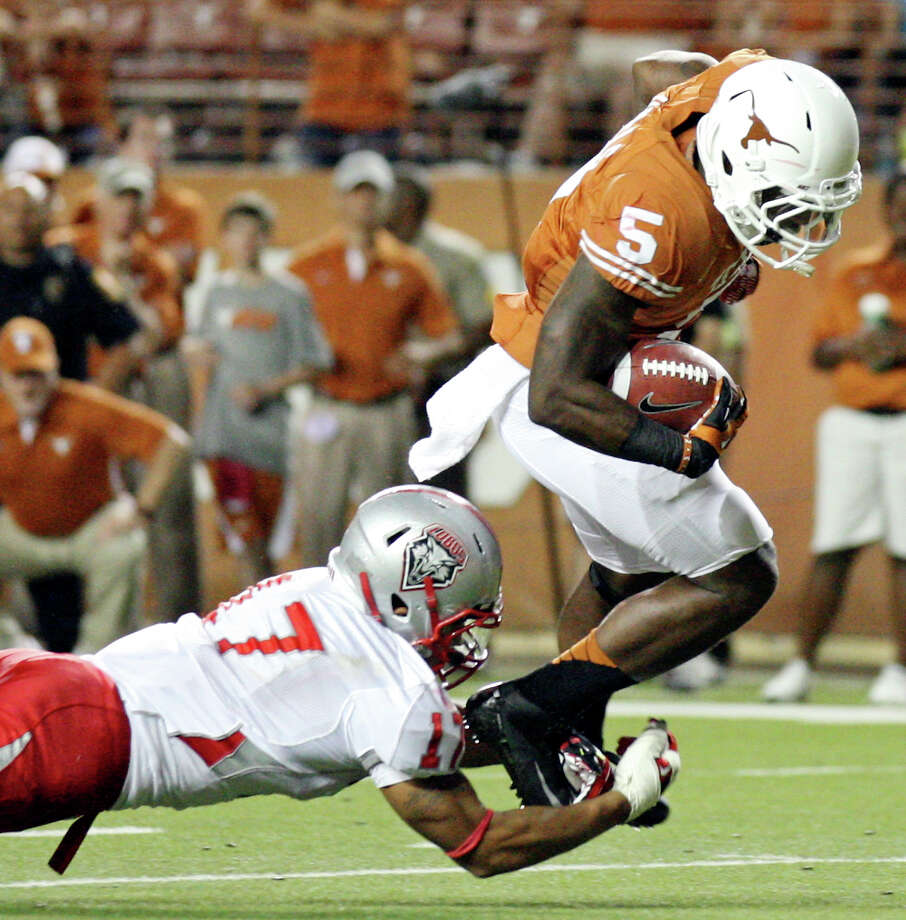 Texas Longhorns' Jeremy Hills tries to shake the tackle of New Mexico Lobos' Freddie Young during second half action Saturday Sept. 8, 2012 at Texas Memorial Stadium in Austin, Tx. The Longhorns won 45-0. Photo: Edward A. Ornelas, Express-News / © 2012 San Antonio Express-News