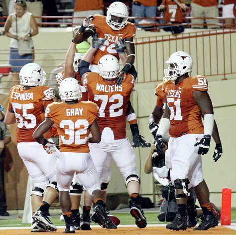Texas Longhorns' Mason Walters celebrates with teammate Texas Longhorns' D.J. Monroe (top) after Monroe scored a touchdown against the New Mexico Lobos during second half action Saturday Sept. 8, 2012 at Texas Memorial Stadium in Austin, Tx. The Longhorns won 45-0. Photo: Edward A. Ornelas, Express-News / © 2012 San Antonio Express-News