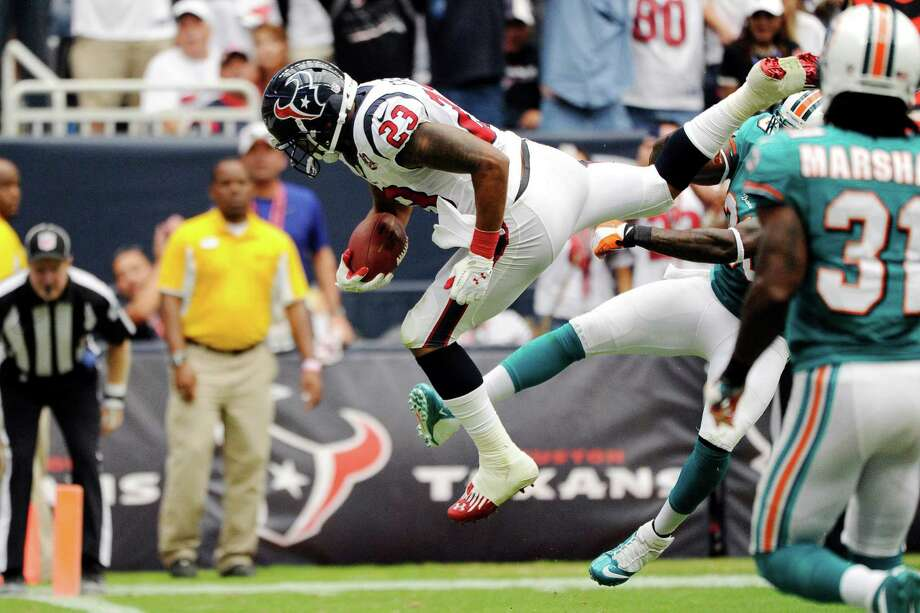 Houston Texans running back Arian Foster (23) leaps into the end zone for a touchdown as Miami Dolphins defensive back Chris Clemons, right, tries to tackle him in the second quarter of an NFL football game, Sunday, Sept. 9, 2012, in Houston. Photo: Dave Einsel