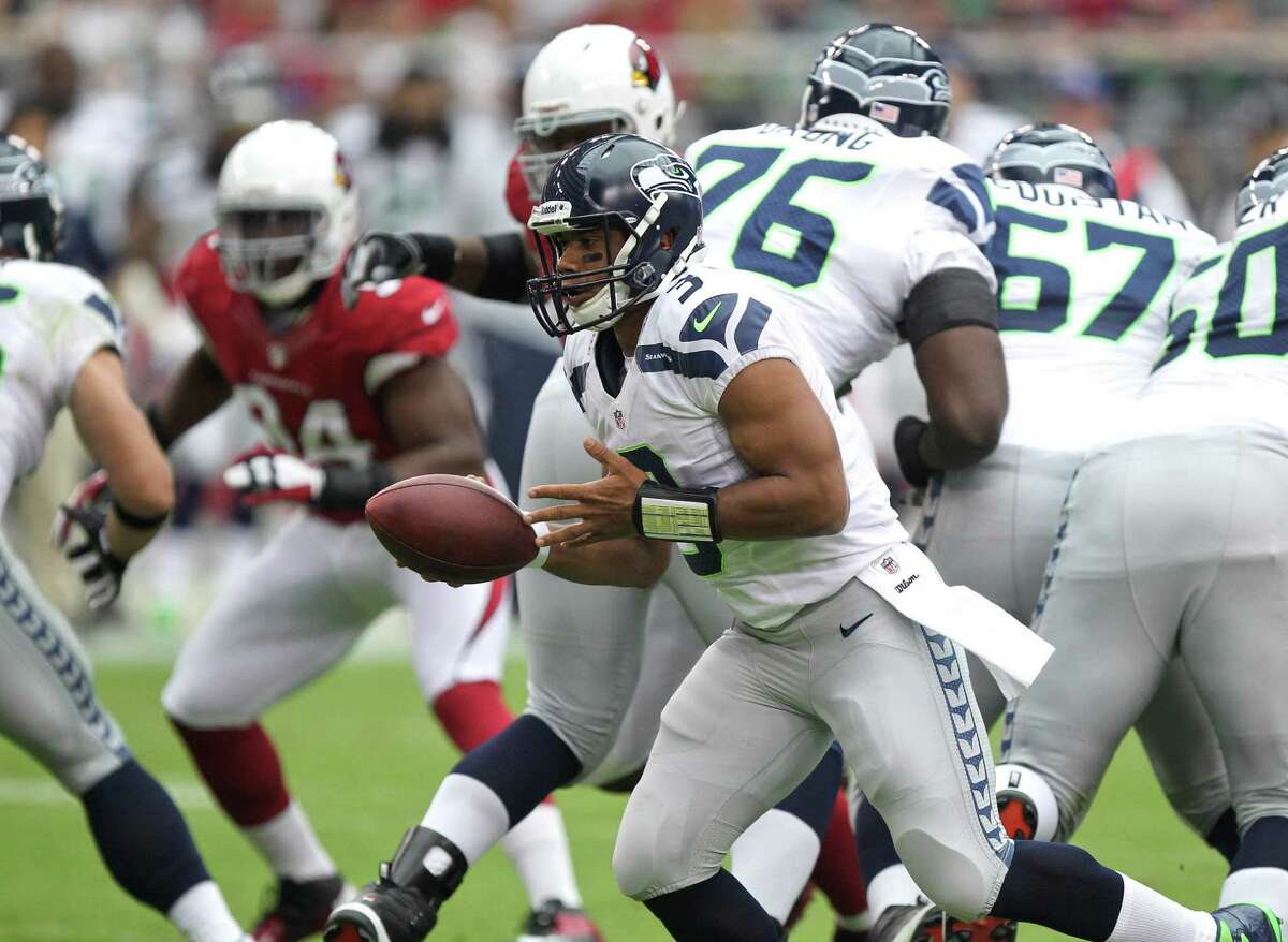 Seattle Seahawks quarterback Russell Wilson (3) hands off against the Arizona Cardinals during the first half of an NFL football game, Sunday, Sept. 9, 2012,in Glendale, Ariz.