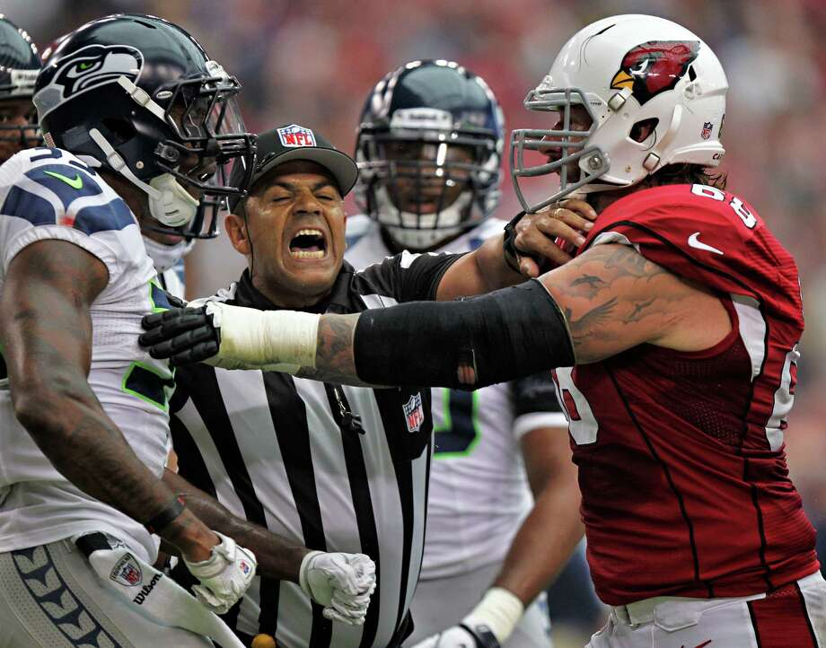 Arizona Cardinals tackle Adam Snyder, right, and Seattle Seahawks defensive back Jeron Johnson are separated by an official during the first half of their NFL football game, Sunday, Sept. 9, 2012, in Glendale, Ariz. Photo: AP