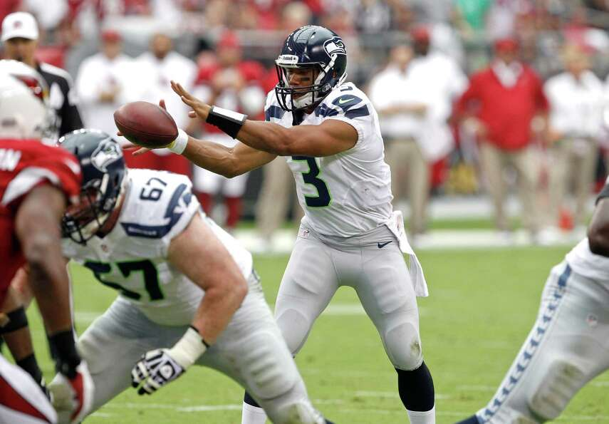 Seattle Seahawks quarterback Russell Wilson (3) takes the snap against the Arizona Cardinals during