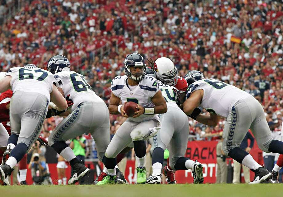 Seattle Seahawks quarterback Russell Wilson (3) hands off against the Arizona Cardinals during the first half of an NFL football game, Sunday, Sept. 9, 2012,in Glendale, Ariz. Photo: AP