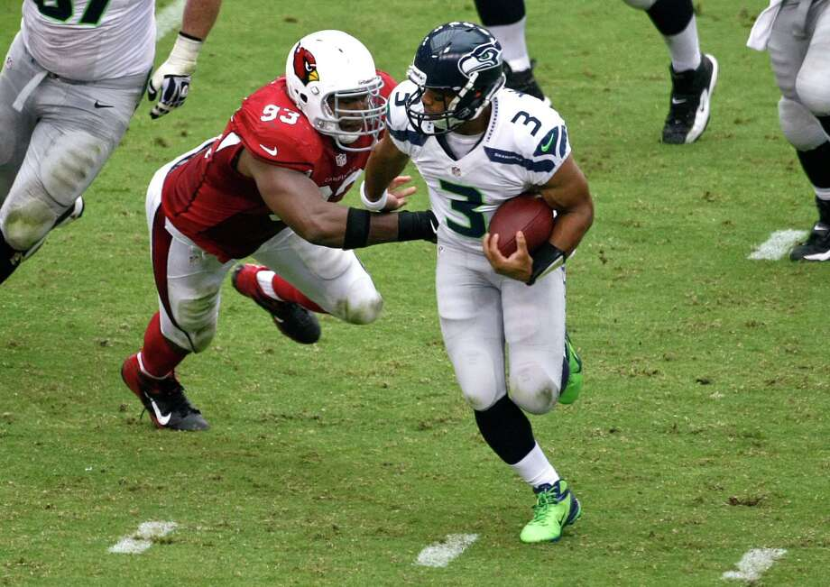Seattle Seahawks quarterback Russell Wilson (3) tries to escape the reach of Arizona Cardinals defensive end Calais Campbell (93) during the first half of an NFL football game, Sunday, Sept. 9, 2012,in Glendale, Ariz. Photo: AP