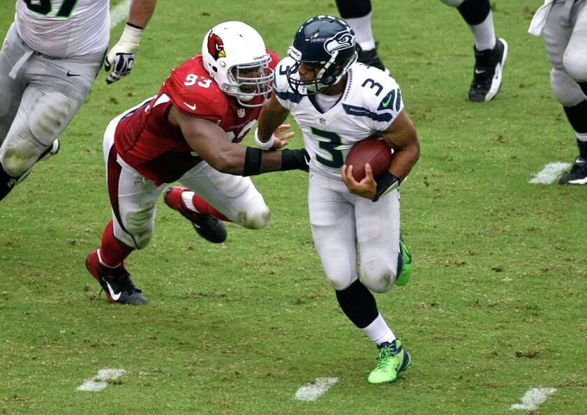 Seattle Seahawks quarterback Russell Wilson (3) tries to escape the reach of Arizona Cardinals defen