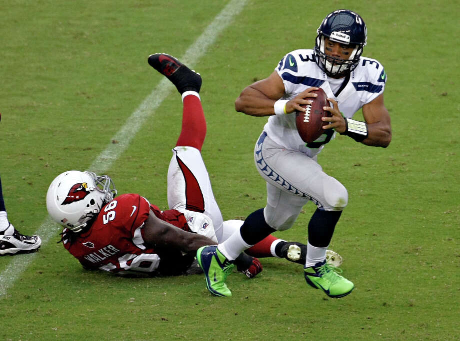 Seattle Seahawks quarterback Russell Wilson (3) escapes the reach of Arizona Cardinals linebacker Reggie Walker (56) during the first half of an NFL football game, Sunday, Sept. 9, 2012, in Glendale, Ariz. Photo: AP