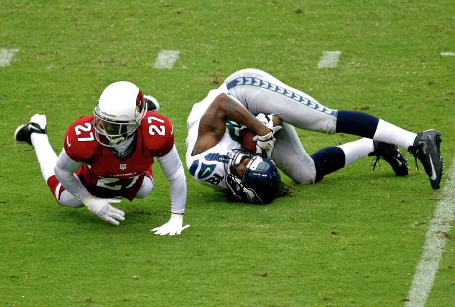 Seattle Seahawks wide receiver Sidney Rice (18) is upended by Arizona Cardinals defensive back Michael Adams (27) during the first half of an NFL football game, Sunday, Sept. 9, 2012,in Glendale, Ariz. Photo: AP