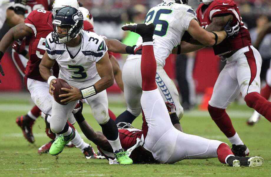 Seattle Seahawks quarterback Russell Wilson, left, breaks the tackle of Arizona Cardinals linebacker Reggie Walker during the first half of an NFL football game, Sunday, Sept. 9, 2012,in Glendale, Ariz. Photo: AP