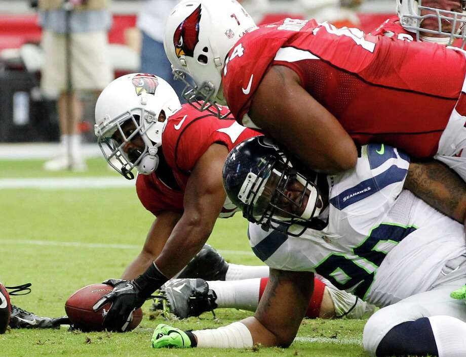 Arizona Cardinals' LaRod Stephens-Howling, left, scores a touchdown as Cardinals' D'Anthony Batiste blocks Seattle Seahawks' Jason Jones, bottom right, during the first half of an NFL football game, Sunday, Sept. 9, 2012, in Glendale, Ariz. Photo: AP