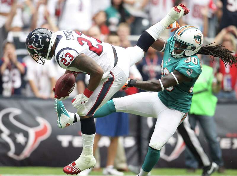Houston Texans running back Arian Foster leaps past Miami Dolphins defensive back Chris Clemons for