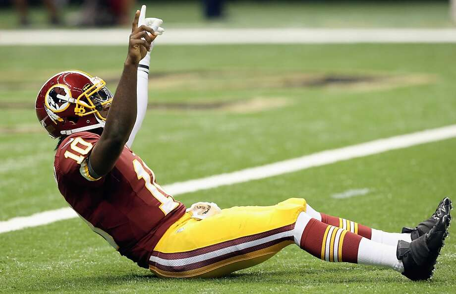 Robert Griffin III, celebrating a touchdown in the Redskins' victory over the Saints, threw for 320 yards and two touchdowns without a pick in his debut. Photo: Ronald Martinez, Getty Images