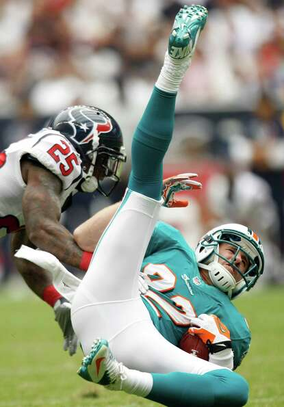 Houston Texans cornerback Kareem Jackson (25) hits Miami Dolphins wide receiver Brian Hartline (82)