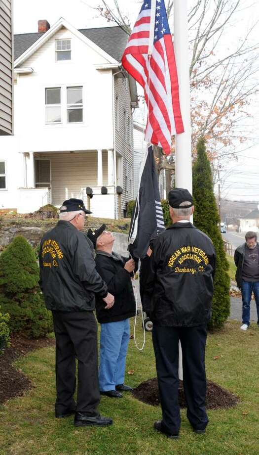 An official ceremony and open house took place at the new Vets House, a transitional facility for veteran's, on New st. in Danbury on Tuesday Dec. 2, 2009. Members of the Korean War Veterans Association raise the American and  POW flags on the flagpole in front of the house during the ceremony. From left, Ray White of Danbury, Bernie Rotunda of Bethel, Brendan Sniffin of Danbury. Photo: Lisa Weir / The News-Times