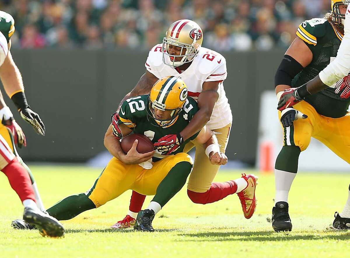 GREEN BAY, WI - SEPTEMBER 09: Aaron Rodgers #12 of the Green Bay Packers is sacked by Jerron McMillian #22 of the San Francisco 49ers during the NFL season opener at Lambeau Field on September 9, 2012 in Green Bay, Wisconsin. (Photo by Andy Lyons/Getty Images)