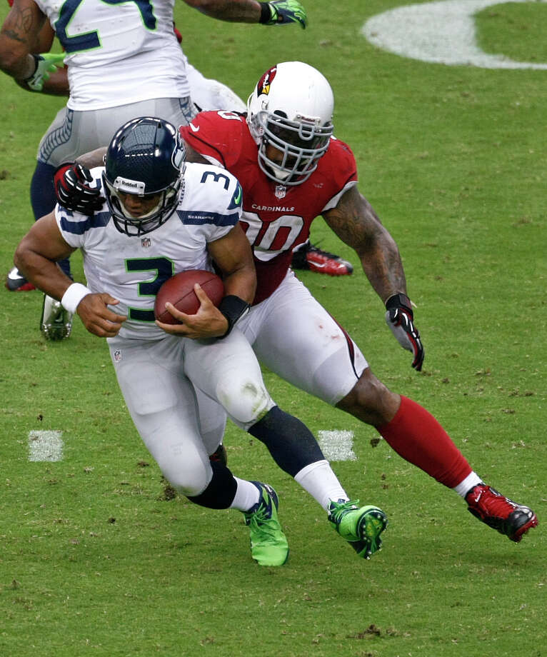 Seattle Seahawks quarterback Russell Wilson (3) tries to escape the reach of Arizona Cardinals defensive tackle Darnell Dockett (90) during the first half of an NFL football game, Sunday, Sept. 9, 2012,in Glendale, Ariz. (AP Photo/Rick Scuteri) Photo: Rick Scuteri, Associated Press / FR157181