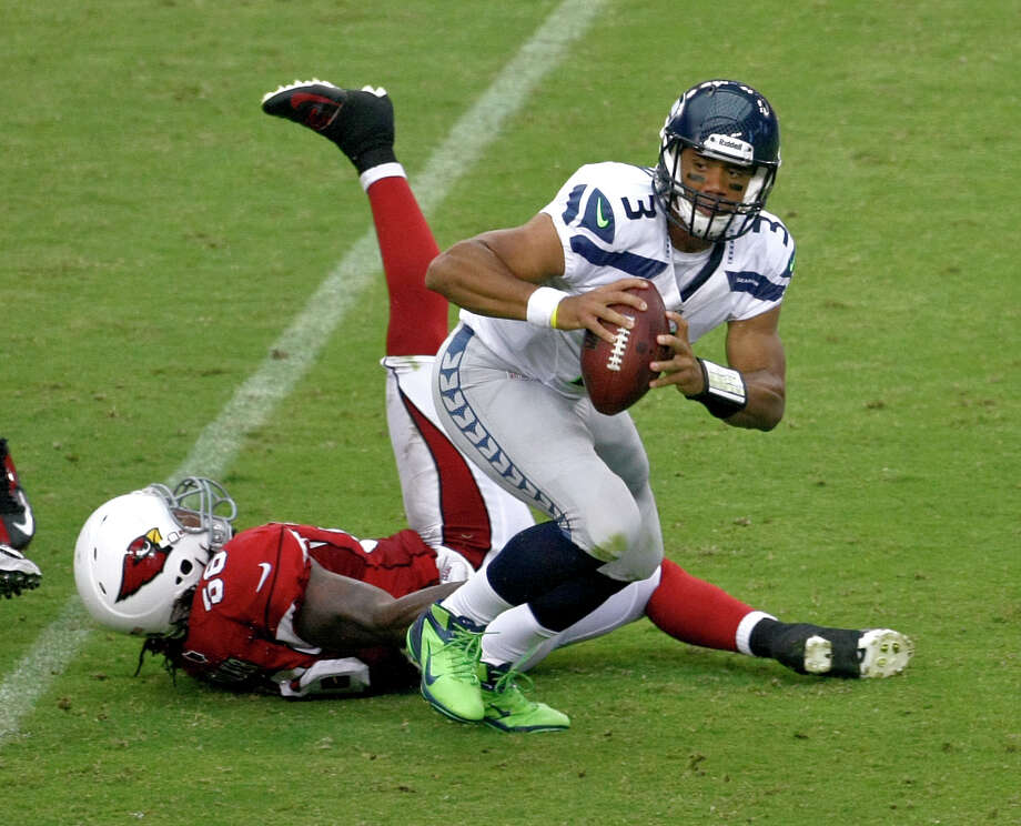 Seattle Seahawks quarterback Russell Wilson (3) escapes a sack by Arizona Cardinals linebacker Reggie Walker during the first half of an NFL football game, Sunday, Sept. 9, 2012,in Glendale, Ariz. (AP Photo/Rick Scuteri) Photo: Rick Scuteri, Associated Press / FR157181