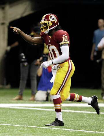 Washington Redskins quarterback Robert Griffin III (10) celebrates in the first half of an NFL football game against the New Orleans Saints  at the Mercedes-Benz Superdome in New Orleans, Sunday, Sept. 9, 2012. (AP Photo/Matthew Hinton) Photo: Matthew Hinton, Associated Press / FR170690 AP