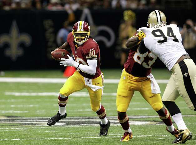 Washington Redskins quarterback Robert Griffin III (10) around New Orleans Saints defensive end Cameron Jordan (94) in the second half of an NFL football game at the Mercedes-Benz Superdome in New Orleans, Sunday, Sept. 9, 2012. (AP Photo/Matthew Hinton) Photo: Matthew Hinton, Associated Press / FR170690 AP