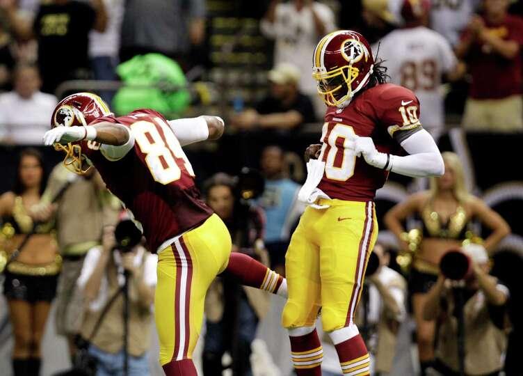 Washington Redskins quarterback Robert Griffin III (10) celebrates a touchdown with tight end Niles