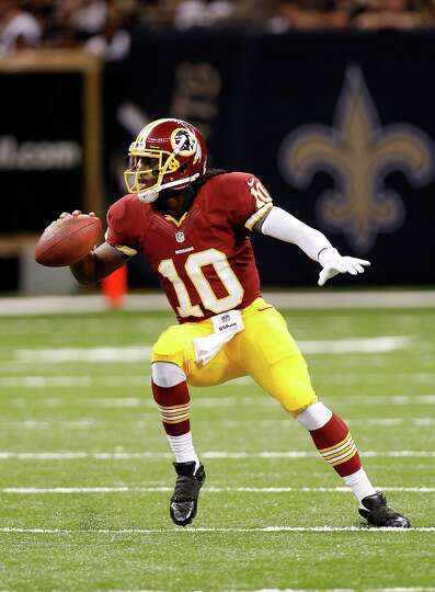 Washington Redskins quarterback Robert Griffin III (10) rushes in the first half of an NFL football