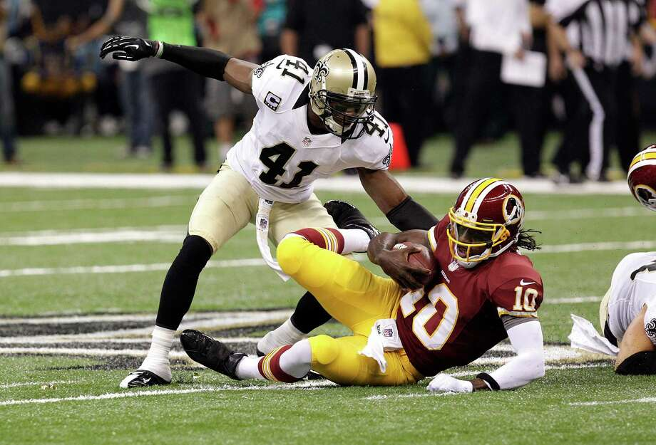 Washington Redskins quarterback Robert Griffin III (10) hits the turf in the second half of an NFL football game as New Orleans Saints strong safety Roman Harper (41) covers at the Mercedes-Benz Superdome in New Orleans, Sunday, Sept. 9, 2012. (AP Photo/Matthew Hinton ) Photo: Matthew Hinton, Associated Press / FR170690 AP