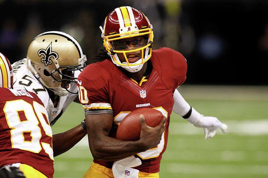 Washington Redskins quarterback Robert Griffin III (10) rushes past New Orleans Saints linebacker David Hawthorne (57) in the first half of an NFL football game against the New Orleans Saints at the Mercedes-Benz Superdome in New Orleans, Sunday, Sept. 9, 2012.  (AP Photo/Bill Haber) Photo: Bill Haber, Associated Press / FR170136 AP