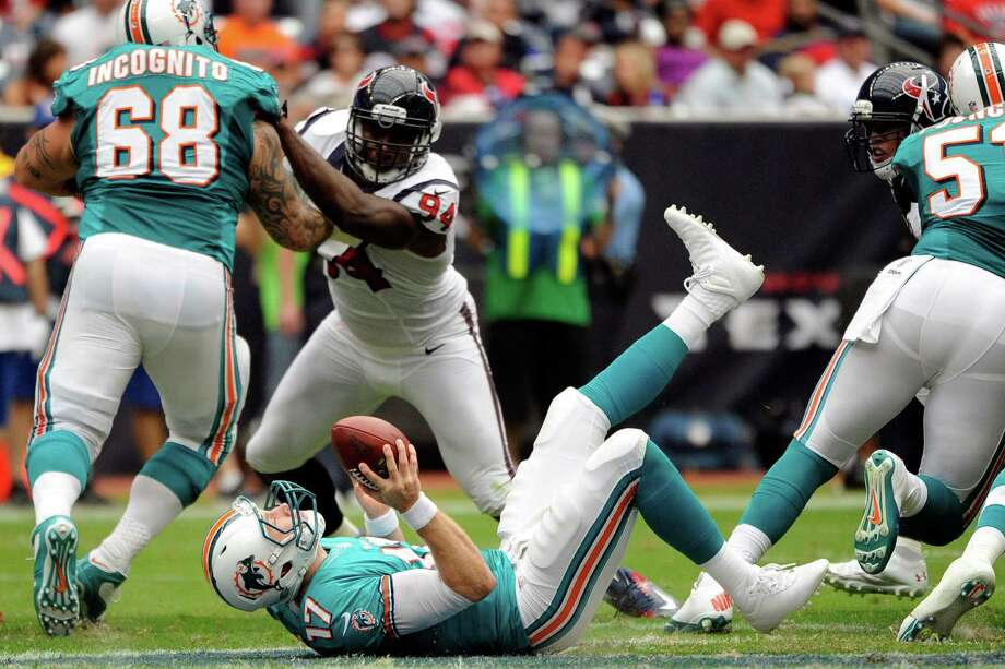 Miami Dolphins quarterback Ryan Tannehill (17) trips and falls to the ground after taking the snap as center Richie Incognito (68) blocks Houston Texans defensive end Antonio Smith (94) in the second quarter of an NFL football game, Sunday, Sept. 9, 2012, in Houston. (AP Photo/Dave Einsel) Photo: Dave Einsel, Associated Press / FR43584 AP