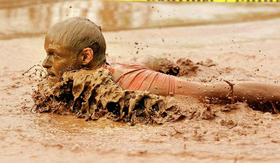 Jonathan Radcliffe swims through the final mud pit during the 2012 Big Country Mudslinger Fun Run on Saturday morning, Sept. 8, 2012, at Seabee Park in Abilene, Texas. Almost 1,400 people participated in the 3 mile long obstacle course which included an eight-foot wall climb, a tire run, balance beam and the mud pit at the end. (AP Photo/The Abilene Reporter-News, Tommy Metthe) MANDATORY CREDIT: TOMMY METTHE/ABILENE REPORTER-NEWS Photo: Thomas Metthe, Associated Press / The Abilene Reporter-News
