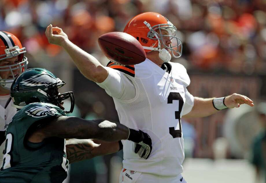 Cleveland Browns quarterback Brandon Weeden (3) has the ball knocked from his hand by Philadelphia Eagles defensive end Trent Cole in the first quarter of an NFL football game Sunday, Sept. 9, 2012, in Cleveland. The play was nullified on a defensive penalty. (AP Photo/Mark Duncan) Photo: Mark Duncan, Associated Press / AP