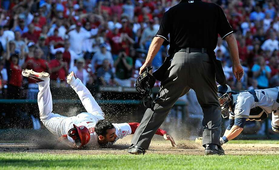 Matt Carpenter singled with one out in the St. Louis 10th off Kameron Loe and moved up on a wild pitch. Craig singled and Carpenter made a nifty slide to score, right. Photo: Jeff Curry, Getty Images