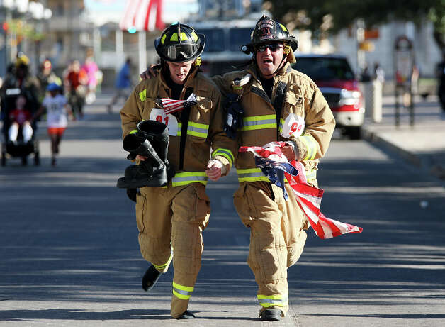 Alamo Heights Fire fighters Michael Dunnam, (cq), left, and Eliab Garcia help each other as they participate in the Stephen Siller Tunnel to Towers Run San Antonio 5K at Alamo Plaza, Sunday, Sept. 9, 2012. The top runner in each division will compete in the Tunnel to Towers run in New York City. Siller was a firefighter with the Brooklyn's Squad 1 and died during the attack on the Twin Towers. Photo: Jerry Lara, San Antonio Express-News / © 2012 San Antonio Express-News