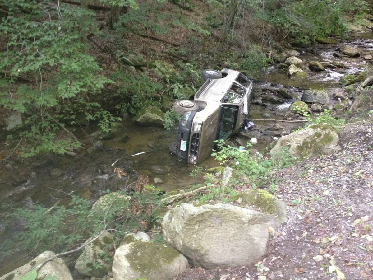 A car rests in the brook at Macedonia State Park on Sunday afternoon. Police said the driver had to be rescued from the vehicle before being transported to New Milford Hospital.