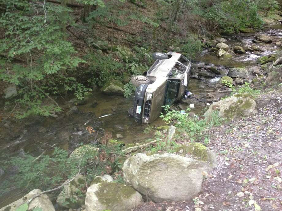 A car rests in the brook at Macedonia State Park on Sunday afternoon. Police said the driver had to be rescued from the vehicle before being transported to New Milford Hospital. Photo: Contributed