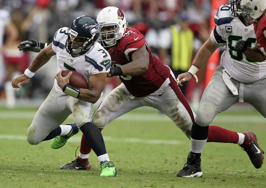 Seattle Seahawks quarterback Russell Wilson (3) tries to escape the reach of Arizona Cardinals defensive end Calais Campbell during the second half of an NFL football game, Sunday, Sept. 9, 2012,in Glendale, Ariz. The Cardinals won 20-16. Photo: AP